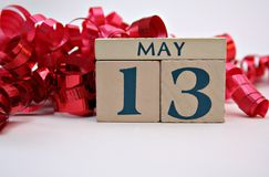 May 13b. Wooden calendar blocks with May 13 and curling red ribbon, Mother's Day Stock Photo