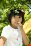 May Crown. A cute Asian girl wears a spring crown of flowers against a backdrop dominated by green leaves Stock Image