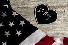 27 May date in black heart and united states flag. Overhead picture of united states flag and black heart including the date 27 May inside, all over wood table royalty free stock images