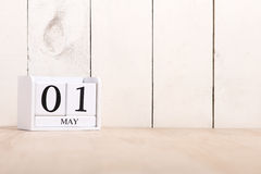 May Day, May 1. May 1st. White wooden blocks with black chalkboard over sandy background. Labor day or holiday concept Stock Photos