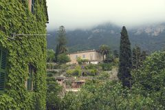 10 May 2018 Deia, Majorca. Beautiful country houses and lush greenery and palm trees in cloudy day. Selective focus royalty free stock images