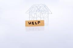 Mały depeszujący metalu modela dom POMAGAMY i słowo Zdjęcie Stock