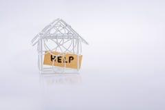 Mały depeszujący metalu modela dom POMAGAMY i słowo Obrazy Royalty Free