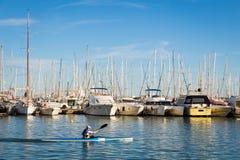 13-MAY-2016 En man som kayaking längs rader av yachter på de Palma lodisarna Arkivfoton