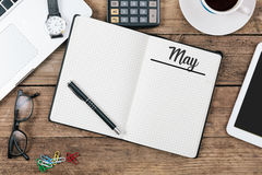 May, English month name on paper note pad at office desk. May, English month name on notepad, office desk with electronic devices, computer and paper, wood table stock photography