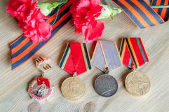 9 May festive composition - jubilee medals of Great patriotic war with red carnations and St George ribbon. 9 May Victory day festive card with jubilee medals of Stock Photography