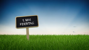 May first holiday sign in green grass. May first holiday text in white chalk on blackboard sign in flowing green grass under clear blue sky background. German Stock Photos