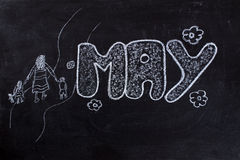 May handwritten on Blackboard. Handwritten May with family on mother day and flowers on black chalkboard Stock Images
