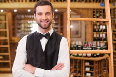 May I help you with wine choosing?. Confident young man in waistcoat and bow tie keeping arms crossed and smiling while standing in liquor store Royalty Free Stock Photography