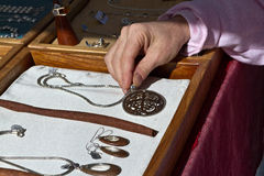 May I See It?. While holiday shopping, examining a necklace laid out in a showcase box at the crafts fair stand of an artisan jewelry maker royalty free stock photo
