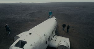 25 MAY 2017, ICELAND. Aerial view of wrecked plane DC-3 in black sand in Iceland. Copter flying over crowd of tourists. 25 MAY 2017, ICELAND. Aerial view of the stock video