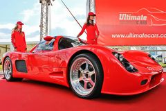 May 29, 2012. Kiev, Ukraine; Ultima GTR720 with beautiful girls in red royalty free stock images