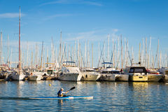 13-MAY-2016. A man kayaking along rows of yachts at the Palma ba Stock Photos