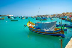 Malta. Beautiful view on the traditional eyed colorful boats Luzzu in the Harbor of Mediterranean fishing village Marsaxlokk, Malt. May 20, 2018. Marsaxlokk Royalty Free Stock Image
