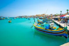 Malta. Beautiful view on the traditional eyed colorful boats Luzzu in the Harbor of Mediterranean fishing village Marsaxlokk, Malt. May 20, 2018. Marsaxlokk Royalty Free Stock Photography