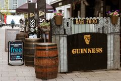 A typical Irish bar on the streets of Cork with Guinness signs and wood barrels outside. May 3rd, 2018, Cork, Ireland - a typical Irish bar on the streets of Stock Photo