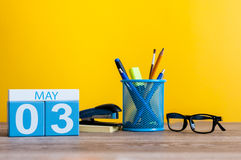 May 3rd. Day 3 of month, calendar on business office table, workplace at yellow background. Spring time Stock Image