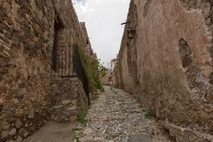 Real de Catorce Mexico narrow cobblestone street. May 22, 2014 Real de Catorce, Mexico: the stone built houses along the cobblestone streets are mostly abandoned Royalty Free Stock Photography