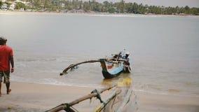 May 5 2018 Sri Lanka Local man sailing to shore in traditional colorful fisherman boat at scenic tropical rural beach.
