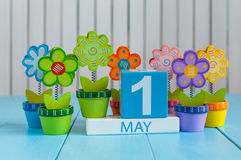 May 1st. Image of may 1 wooden color calendar on white background with flowers. Spring day, empty space for text Royalty Free Stock Image