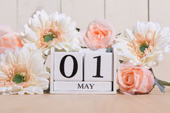 May 1st. Image of may 1 white block calendar on white background with flowers. Spring day, empty space for text. International Workers' Day stock photos