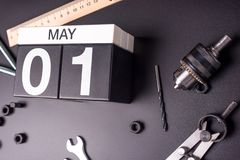 May 1st - Labour day. Day 1 of may month, calendar on black background with workers tools.  royalty free stock photos