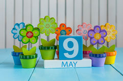 May 9th. Image of may 9 wooden color calendar on white background with flowers. Spring day, empty space for text. Symbols Of the victory in World War II Stock Image