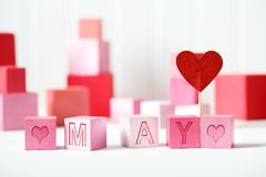 May theme with pink blocks. May theme with pink and red wooden blocks Royalty Free Stock Photos