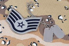 May 12, 2018. US AIR FORCE Staff Sergeant rank patch and dog tags on Desert Battle Dress Uniform background. May 12, 2018. US AIR FORCE Staff Sergeant rank patch royalty free stock photo