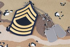 May 12, 2018. US ARMY Master Sergeant rank patch and dog tags on Desert Battle Dress Uniform background. May 12, 2018. US ARMY Master Sergeant rank patch and dog stock image