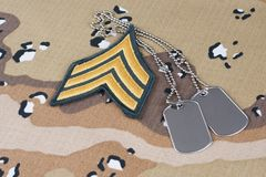 May 12, 2018. US ARMY Sergeant rank patch and dog tags on Desert Battle Dress Uniform background royalty free stock image