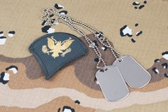 May 12, 2018. US ARMY Specialist rank patch and dog tags on Desert Battle Dress Uniform background royalty free stock image