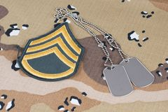 May 12, 2018. US ARMY Staff Sergeant rank patch and dog tags on Desert Battle Dress Uniform background royalty free stock photo