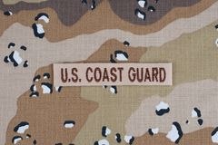 May 12, 2018. US COAST GUARD branch tape on desert camouflage uniform background stock images
