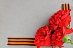 May 9 Victory day card. Red carnations and St. George ribbon on the background of an old photo album. Day of memory and royalty free stock photos