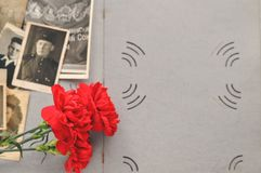 May 9 Victory day card. Red carnations and St. George ribbon on the background of an old photo album with military photos. Day of royalty free stock photos