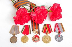 9 May Victory Day festive background - jubilee medal of Great patriotic war with red carnations and St George ribbon. 9 May Victory Day background - jubilee Royalty Free Stock Photo