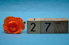 27 May on wooden blocks with an orange rose. On a blue background stock image