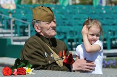 MAY 9: WWII veteran during a parade on victory Day on may 9. MINSK, BELARUS - MAY 9: WWII veteran with a little girl during a parade on victory Day on may 9 Royalty Free Stock Images