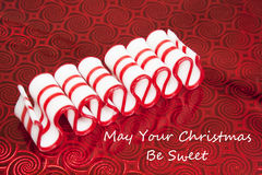 May Your Christmas Be Sweet. This is a delicious red and white striped old fashioned peppermint ribbon Christmas candy on a red foil background stock image
