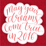 May your dreams come true in 2016. Christmas. Greeting card, dip pen calligraphy at red knitted background Royalty Free Stock Photo