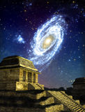 Maya city. A Maya city by night with a galaxy in background in 3D