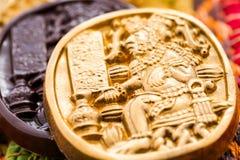 Maya glyphs. Gourmet Maya glyphs in dark chocolate covered with gold dusting Royalty Free Stock Photo