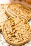 Maya glyphs. Gourmet Maya glyphs in dark chocolate covered with gold dusting Royalty Free Stock Image