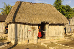 Maya lifestyle. Maya woman in front of a typical mayan house with roof made from palm trees, Yucatan Peninsula, Mexico Royalty Free Stock Images