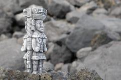 Maya Statue. Ancient Maya Statue on Rocks near the Ocean Stock Photo