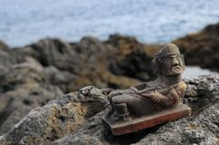 Maya Statue. Ancient Maya Statue on the Rocks near Ocean Royalty Free Stock Image