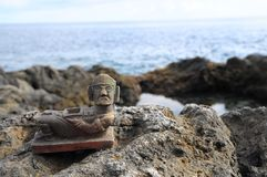 Maya Statue. Ancient Maya Statue on the Rocks near Ocean Royalty Free Stock Photos
