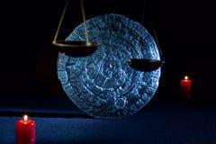 Mayan kalender- och rättvisaskala med stearinljus på svart Arkivbilder
