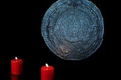 Mayan kalender och röda stearinljus på svart Arkivfoto